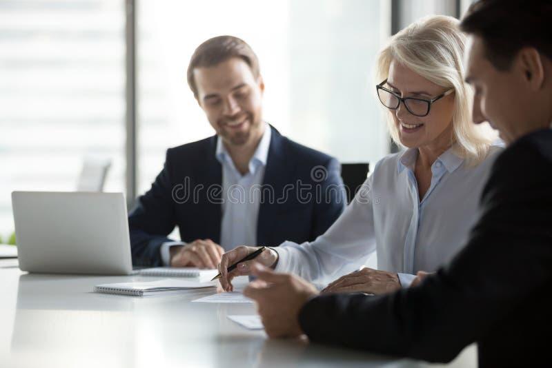 Contratto di carta di firma invecchiato medio sorridente della donna di affari alla riunione dei gruppi fotografia stock libera da diritti