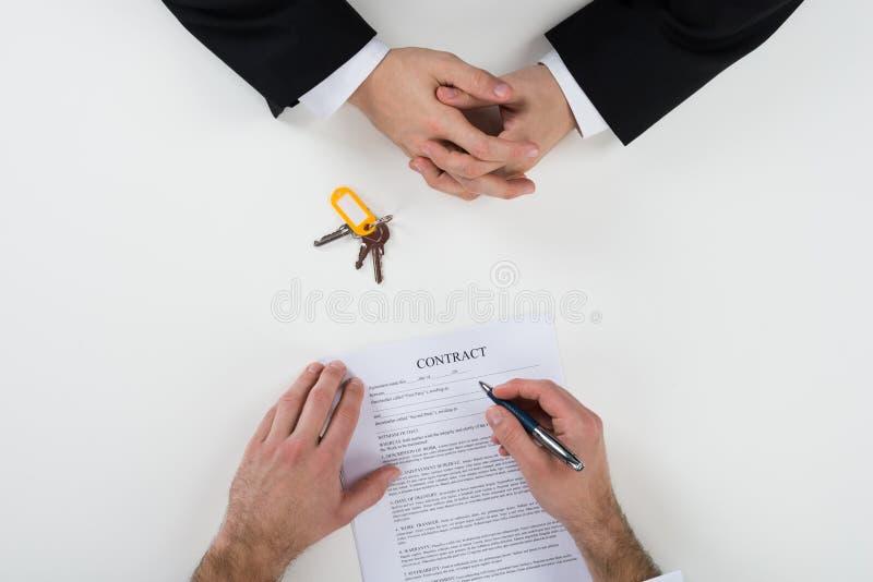 Contratto di With Customer Signing dell'agente immobiliare allo scrittorio fotografia stock libera da diritti