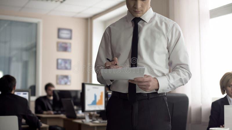 Contratto di firma del capo maschio, impiegati che lavorano al fondo, stile di vita occupato fotografie stock libere da diritti