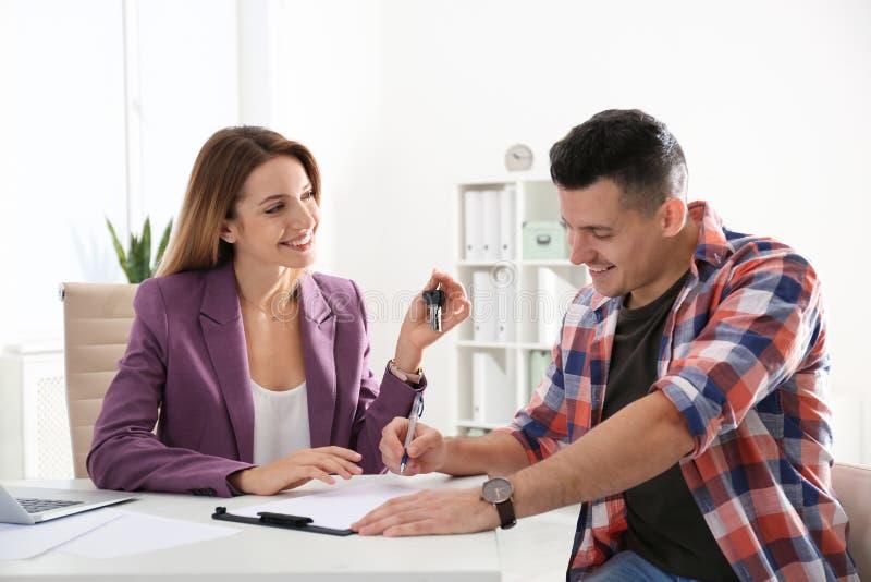 Contratto di firma del cliente con l'agente immobiliare fotografia stock