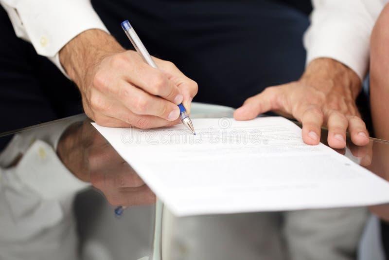 Contratto di firma del giovane uomo d'affari sullo scrittorio fotografia stock libera da diritti