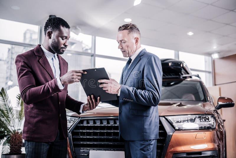Contratto di firma dell'uomo d'affari mentre comprando la nuova automobile marrone della berlina fotografia stock libera da diritti