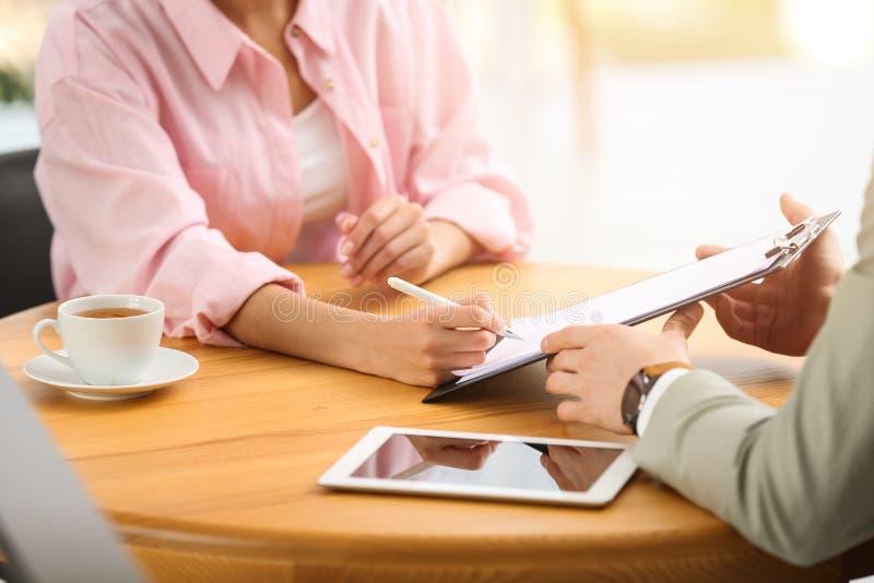 Contratto di firma della donna con l'agente di assicurazione in ufficio fotografie stock