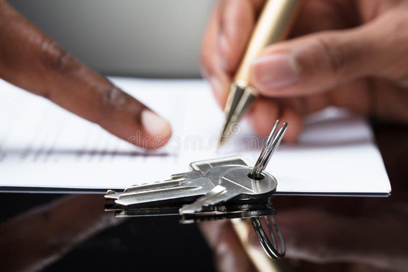 Contratto di firma della mano del ` s della persona con le chiavi su  fotografie stock libere da diritti