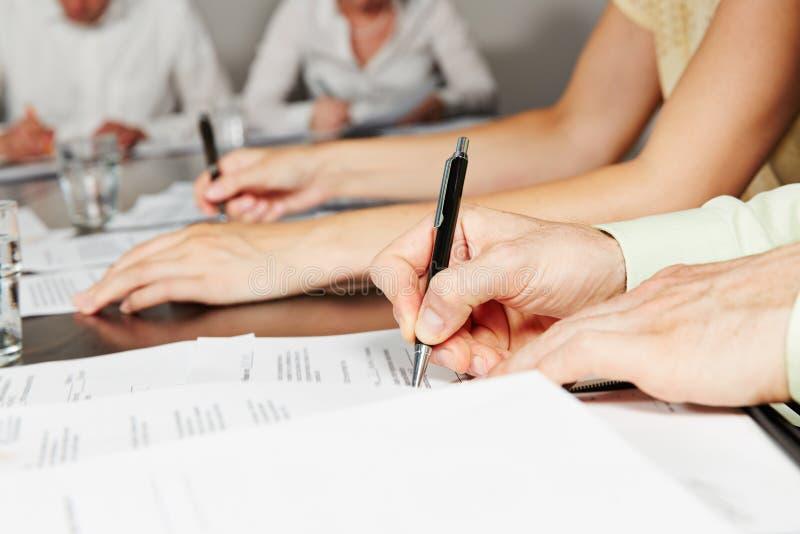 Contratto di firma della mano nella riunione d'affari immagine stock