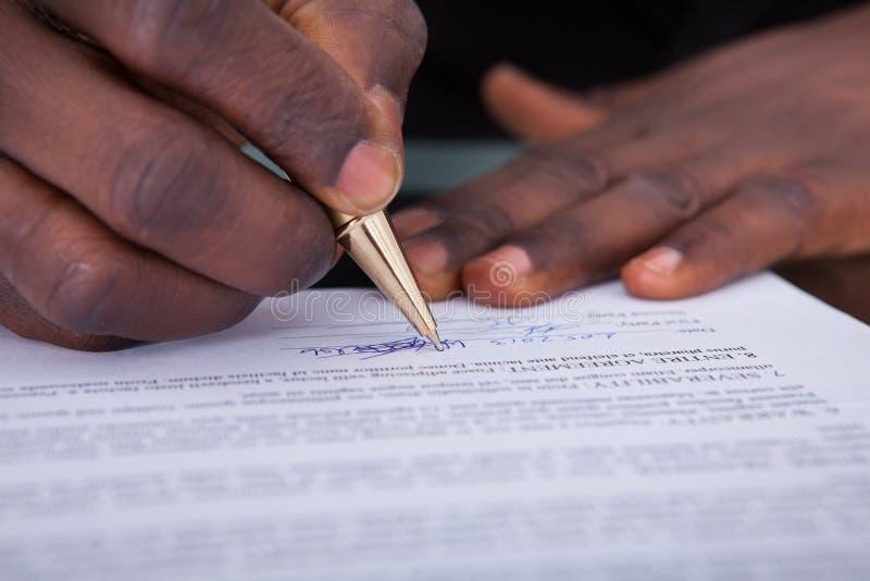 Contratto di firma della persona di affari fotografia stock