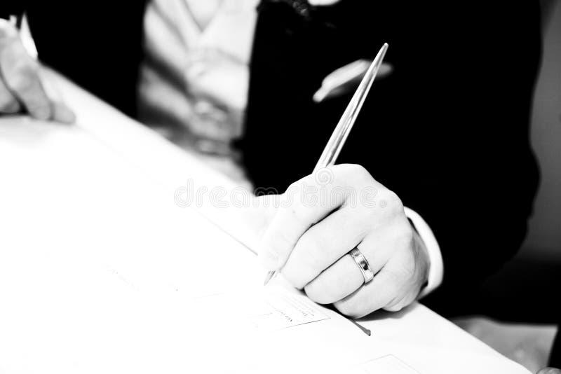 Contratto di sign di cerimonia nuziale dello sposo immagini stock libere da diritti