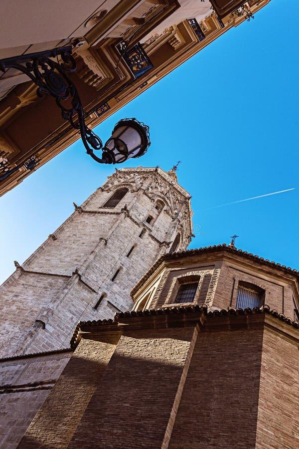 Contre le fond du ciel bleu, la traînée de l'avion, la lanterne sur le coin de la maison et la cathédrale avec la tour de cloche images libres de droits