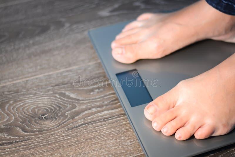 Contribuisca a perdere i chilogrammi con i piedi della donna che fanno un passo su una bilancia fotografia stock