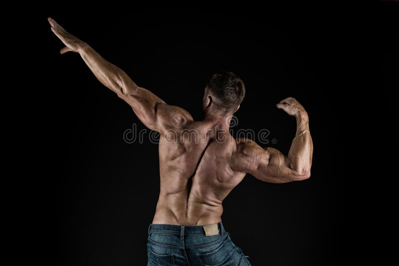 Contributing to well-being through body training. Muscular sportsman after muscle training back view on black background stock images