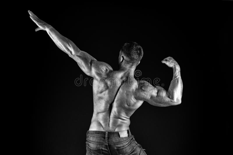 Contributing to well-being through body training. Muscular sportsman after muscle training back view on black background stock photo