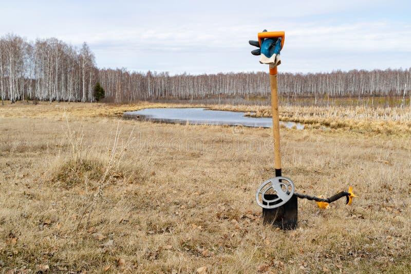 Contro il contesto del lago e del campo c'è pala picchettata nella terra sul metal detector della pala, ferente lo PS immagine stock