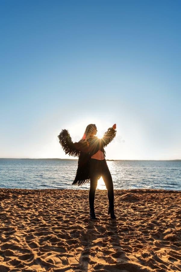 Contro il contesto del sol levante la siluetta di una ragazza di dancing in vestiti neri d'ondeggiamento gradisce un uccello fotografie stock
