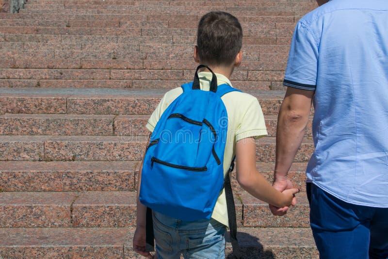 Contro il contesto di una scala, il ragazzo va a scuola, tenendo la sua mano dei padri immagine stock