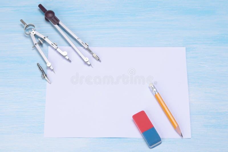 contro lo sfondo del blu la tavola è uno strato bianco e una bussola per la gomma di disegno immagini stock