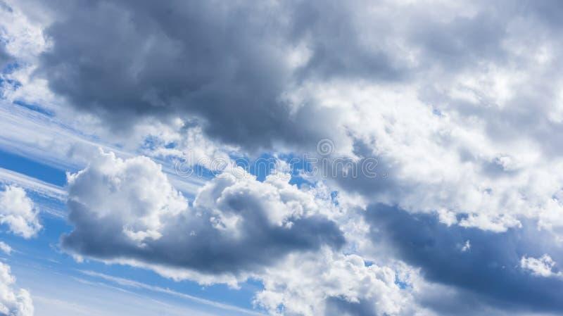 Contro lo sfondo del cielo blu, delle nuvole lanuginose di colore bianco e grigio fotografia stock