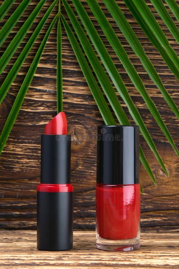 Contro lo sfondo della tavola scura e di legno e della foglia di palma verde, dello smalto rosso e del rossetto luminoso immagini stock