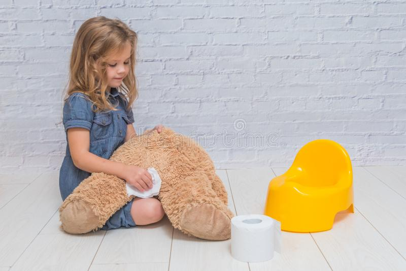 Contro lo sfondo di un muro di mattoni bianco, la ragazza si siede sulla a fotografia stock