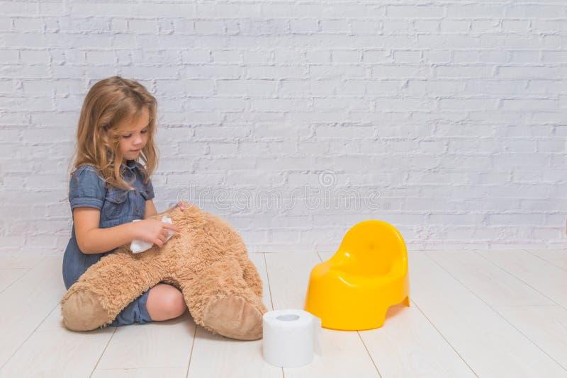 Contro lo sfondo di un muro di mattoni bianco, la ragazza si siede sulla a fotografia stock libera da diritti