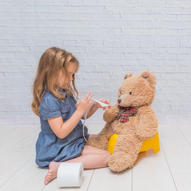 Contro lo sfondo di un muro di mattoni bianco, la ragazza si siede sulla a immagini stock libere da diritti