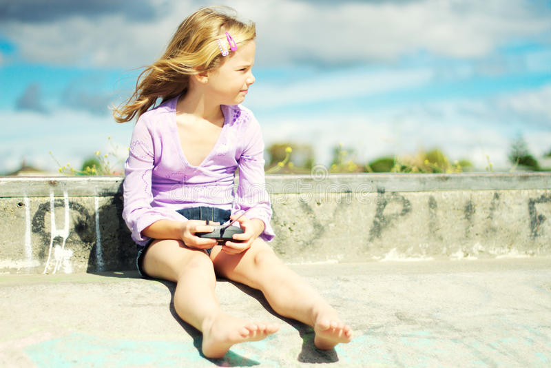 In control. A little girl playing with a remote control for her toy car; cross processed effect stock images
