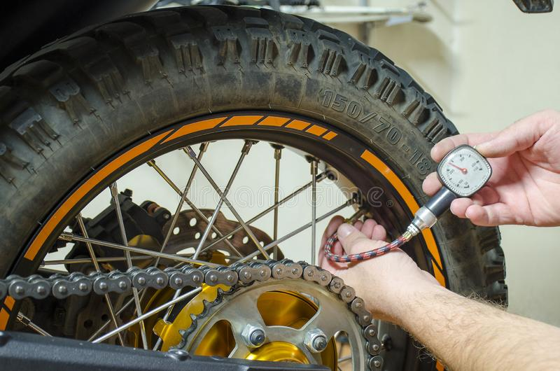 Control air pressure in motorcycle back tire.  royalty free stock photography