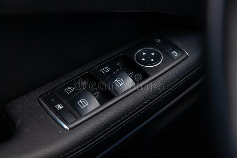 The control buttons for opening and closing windows of doors and electric controls and settings of mirrors on the door in black. With leather upholstery in a royalty free stock image
