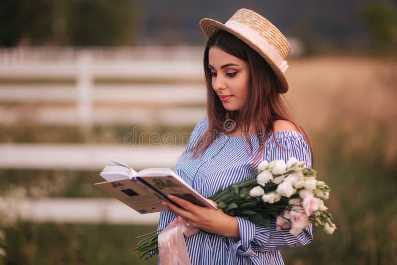 Control de la mujer elegante un libro y un ramo de flor a disposición Ella se coloca en el campo Fondo de la granja Lectura del l imagenes de archivo