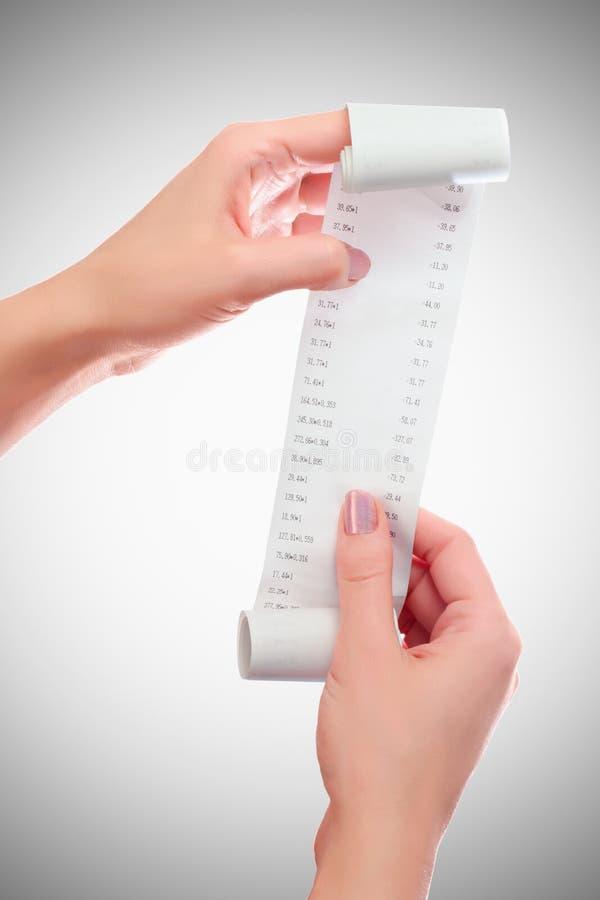 Control de la mujer o de la muchacha en el rollo de las manos del papel con mofa impresa del recibo encima de la plantilla Limpie imagenes de archivo