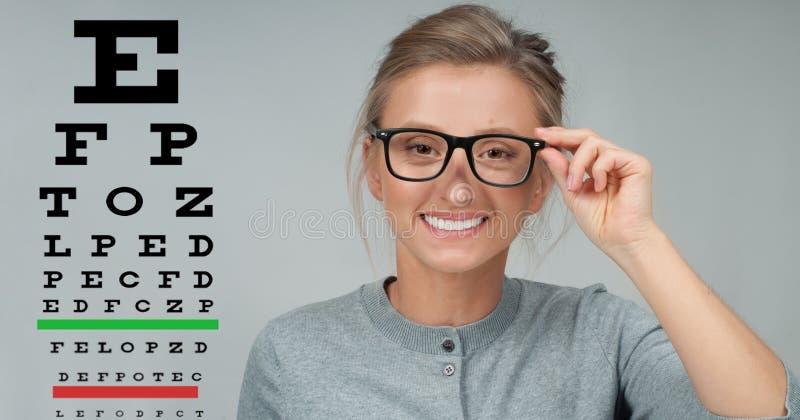 Control de la vista Mujer en vidrios en el fondo de la carta de prueba del ojo imagen de archivo libre de regalías