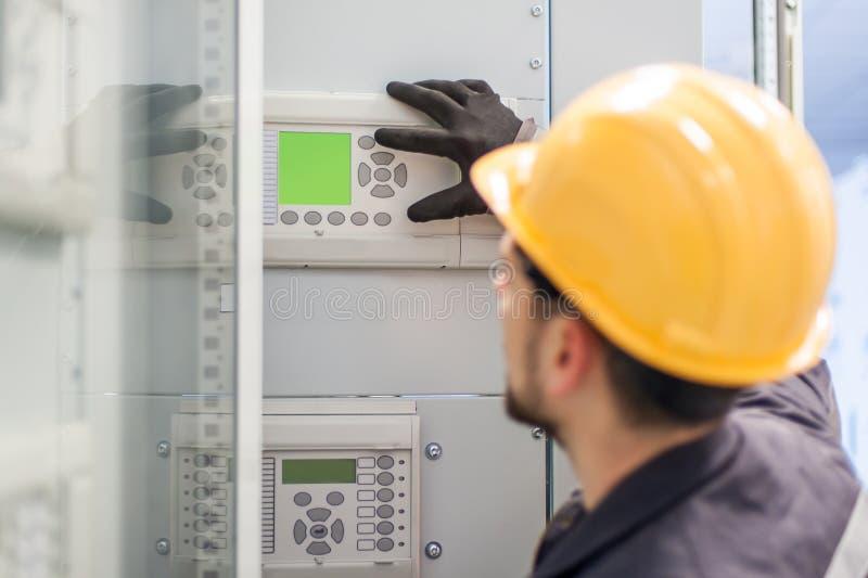 Control del dispositivo de distribución y de la bahía del voltaje de la prueba del ingeniero del mantenimiento foto de archivo libre de regalías