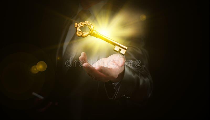Control del hombre de negocios una llave brillante del oro, concepto del negocio fotografía de archivo libre de regalías