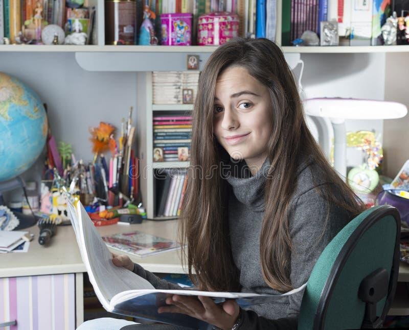 Control del niño un libro estudiar a la muchacha con mirada curiosa imagenes de archivo