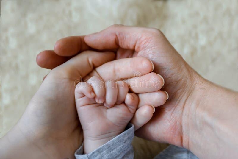 Control del padre y de la madre en sus manos manos poco recién nacidas de un bebé foto de archivo libre de regalías