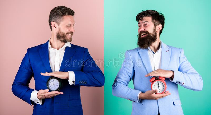 Control and discipline. Build your self discipline. Men business formal suits hold alarm clocks. Lack of self discipline. In time management leads people to royalty free stock image