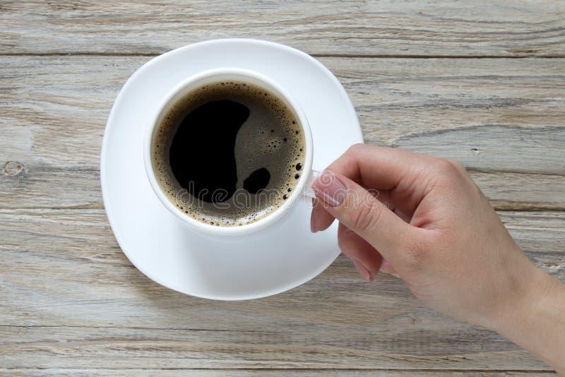 Control femenino de la mano a la taza de café sólo del fondo de madera fotos de archivo