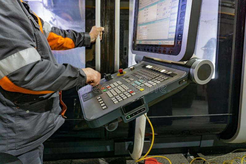 The control panel of a CNC machine, a worker writes a program for processing parts on a machine by cutting.  royalty free stock photography