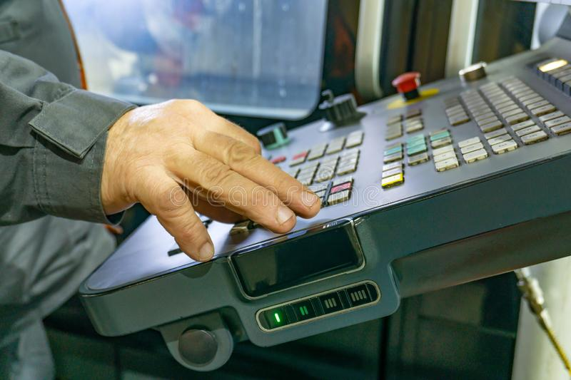 The control panel of a CNC machine, a worker writes a program for processing parts on a machine by cutting.  royalty free stock image