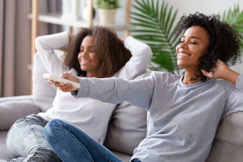 Control remoto afroamericano de la tenencia de la madre, relajándose con la hija imágenes de archivo libres de regalías
