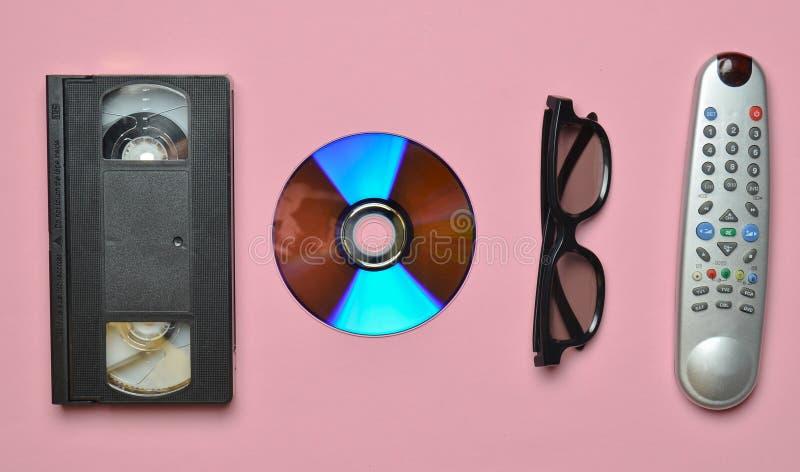 Control remoto, 3d vidrios, CD, cinta de video en un fondo en colores pastel rosado Tecnología retra imagen de archivo