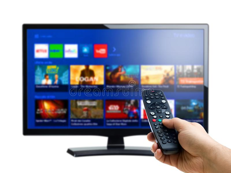 Control remoto de la mano que señala en Internet o la exhibición a pedido de la TV imagen de archivo