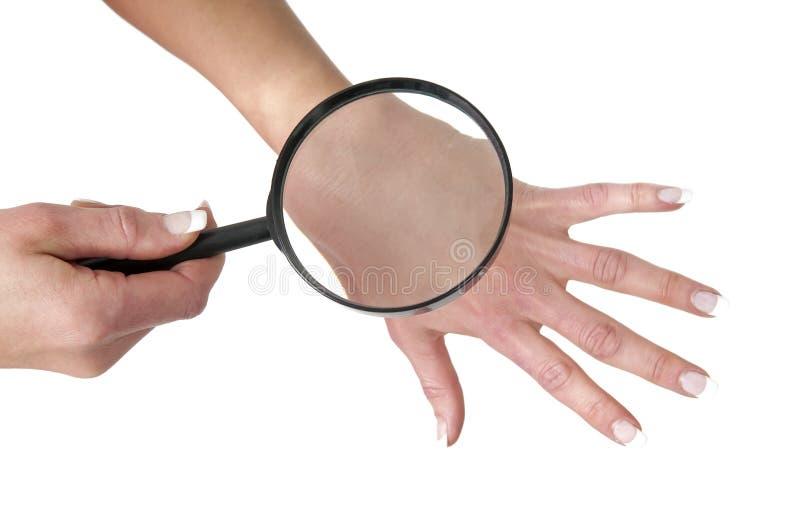 Control sano de la piel en la mano de la mujer con la lupa fotos de archivo libres de regalías