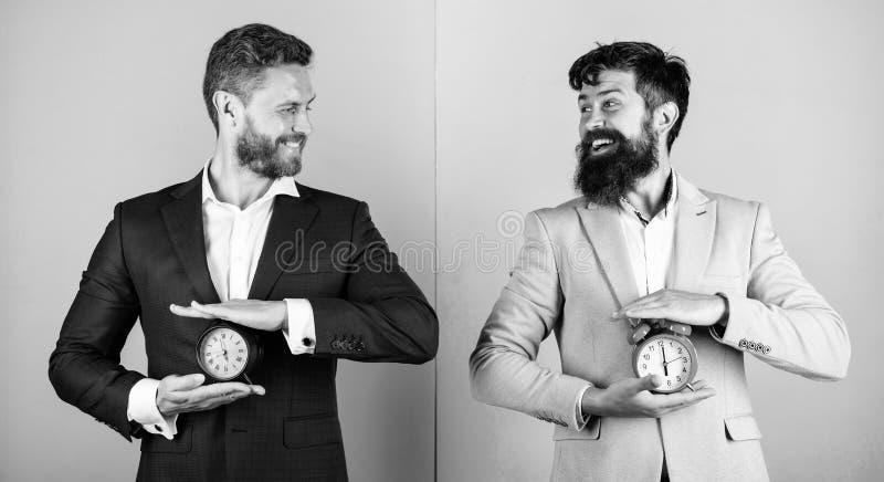 Control y disciplina Construya su autodisciplina Los trajes formales del negocio de los hombres sostienen los despertadores Falta foto de archivo libre de regalías
