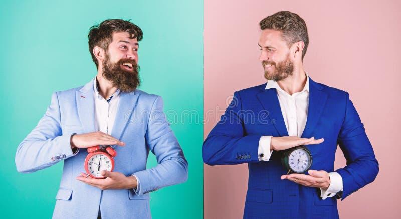 Control y disciplina Construya su autodisciplina Los trajes formales del negocio de los hombres sostienen los despertadores Falta fotos de archivo