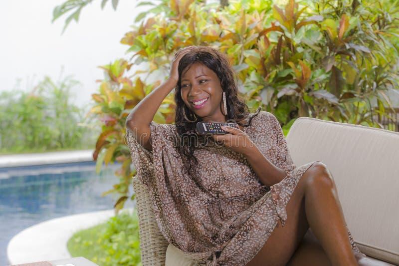 Controlador de observação novo da terra arrendada da televisão da mulher americana elegante feliz e atrativa do africano negro qu imagens de stock