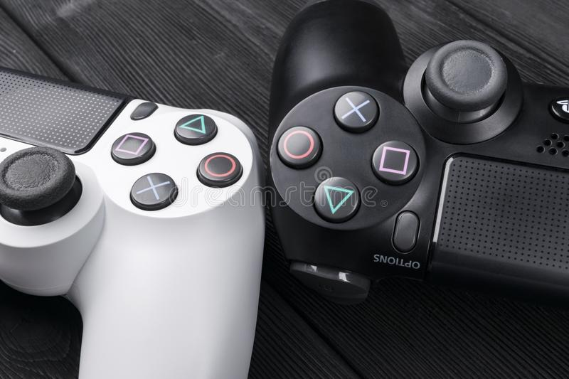 Controlador do jogo da revisão 1Tb magro de Sony PlayStation 4 e dos 2 dualshock no fundo de madeira da tabela Console do jogo de fotografia de stock royalty free