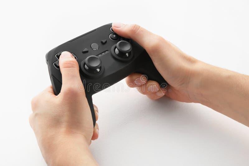 Controlador do jogo de vídeo da terra arrendada da jovem mulher no fundo branco foto de stock royalty free