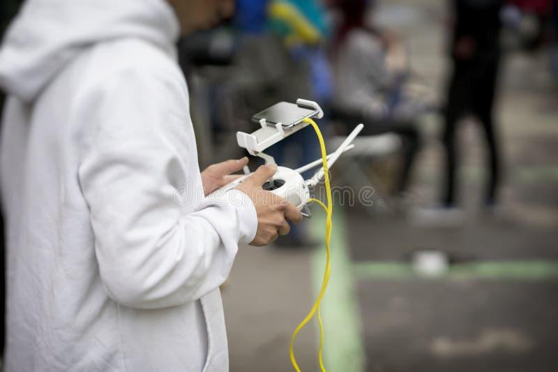 Controlador remoto, auriculares com o smartphone nas mãos do adolescente, close-up do homem novo, zangão de pilotagem do voo Brin fotografia de stock royalty free