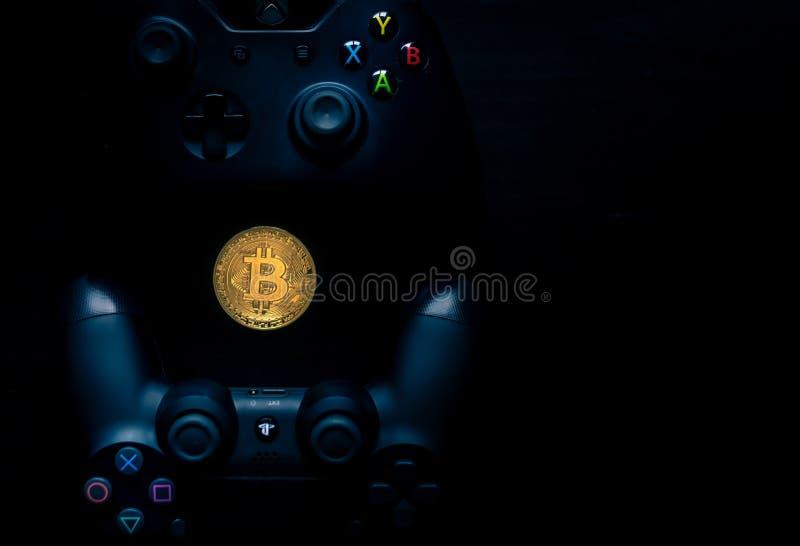 Controladores de Playstation e de Xbox ao lado de um Bitcoin f?sico imagem de stock