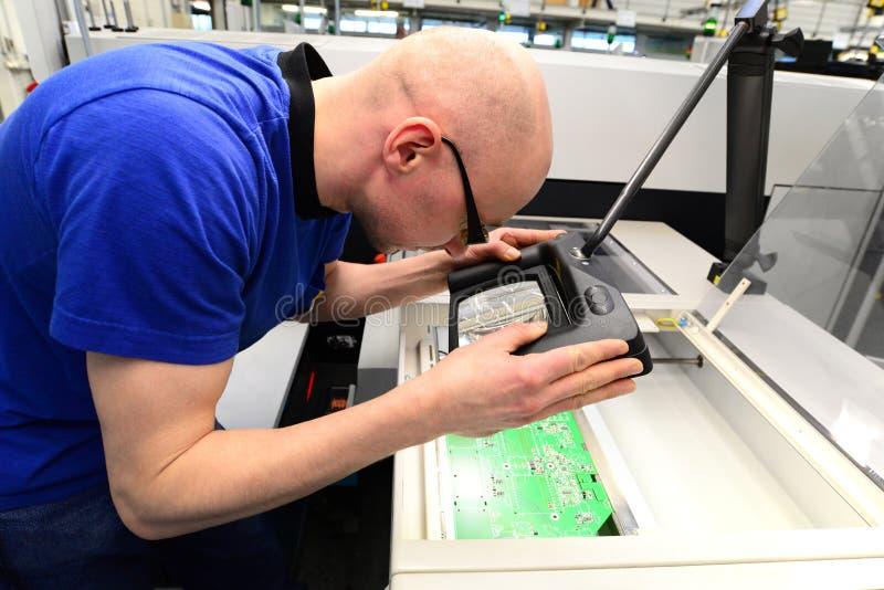 Controle da qualidade na produção - o homem verifica a placa para ver se há defeitos imagens de stock royalty free